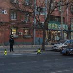 Ausiliario del traffico cinese controlla che nessuno parcheggi nelle strisce appena disegnate, a Guy Delisle sarebbe piaciuto un sacco